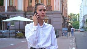 年轻现代妇女在街道上站立,并且谈话在电话,定约会,通信概念,都市概念 影视素材