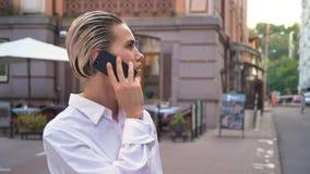 年轻现代妇女在街道上站立,并且谈话在电话,接受任命,通信概念,都市概念 股票视频