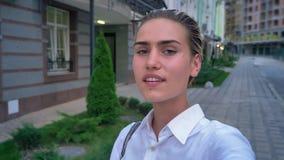 年轻现代妇女在街道上站立,拿着照相机,做selfie,通信概念 股票视频