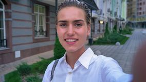 年轻现代妇女在街道上站立,拿着照相机,波浪你好,通信概念 影视素材