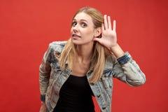 年轻现代时髦的妇女美丽如画投入她的手到她的耳朵在听殷勤或窃听的标志 免版税库存照片