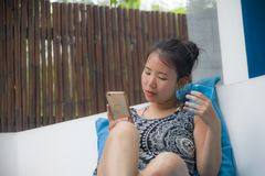 年轻甜和相当亚裔中国妇女在海滩度假胜地使用互联网社会媒介坐手机放松了和 免版税库存图片