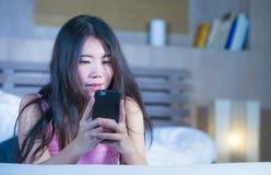 年轻甜和美丽的亚裔中国人20s或30s妇女微笑的愉快说谎在使用互联网手机约会的床上或送 库存图片