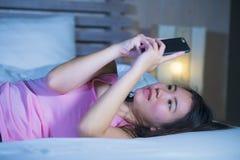 年轻甜和美丽的亚裔中国人20s或30s妇女微笑的愉快说谎在使用互联网手机约会的床上或送 免版税库存照片
