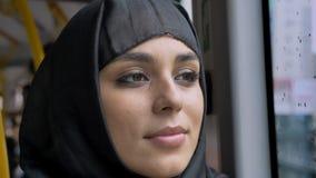 年轻甜回教妇女的面孔hijab的在多雨窗口里在公共汽车,运输概念,都市概念,天气上观看 股票视频