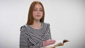 年轻甜镇静姜女孩是阅读书,观看在照相机,白色背景 股票视频
