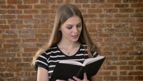 年轻甜blonda是阅读书,拇指throudn页,微笑,砖背景 股票视频