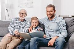 年轻男孩、坐长沙发在客厅和读a的父亲和祖父 免版税库存图片