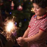 年轻男孩举行灼烧的闪烁发光物和微笑 免版税库存图片