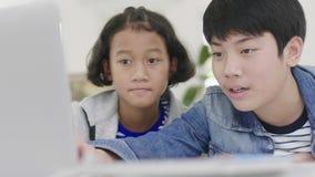年轻男孩使用计算机教和解释家庭作业 对有表情和愉快的姿态的朋友, 股票录像