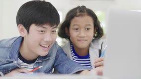 年轻男孩使用计算机教和解释家庭作业 对有表情和愉快的姿态的朋友, 影视素材