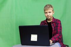 年轻男孩博客作者记录在绿色背景的录影 库存照片