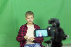 年轻男孩博客作者记录在绿色背景的录影 免版税库存图片