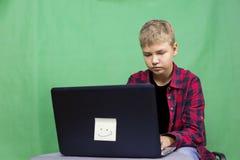 年轻男孩博客作者记录在绿色背景的录影 免版税图库摄影