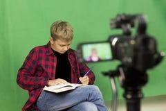 年轻男孩博客作者记录在绿色背景的录影 免版税库存照片