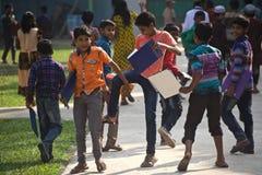 年轻男孩在完成检查以后取笑在学校校园里 图库摄影