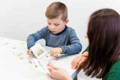 年轻男孩在语言矫正办公室 行使与语言矫治者儿童作业治疗的学龄前儿童正确发音 免版税库存照片