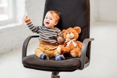 年轻男孩坐办公室椅子 库存照片