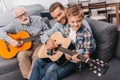 年轻男孩坐长沙发在客厅,弹有他的父亲的吉他 免版税图库摄影
