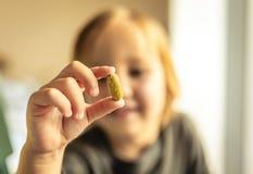 年轻男孩拿着维生素或处方药片与手指在面孔前面 r r ? 免版税库存图片