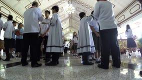 年轻男孩接受天主教教士执行的圣餐的圣礼 影视素材