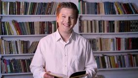 年轻男孩是阅读书在图书馆里,观看在照相机,微笑 影视素材
