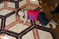 年轻男孩睡着在地板上的一张五颜六色的席子 库存图片