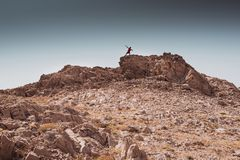 年轻男孩获得乐趣在岩石沙漠自由和冒险生活方式和体育概念 免版税库存照片