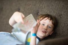 年轻男孩说谎的放松在沙发,当读时 免版税库存图片