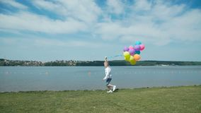 年轻男孩赛跑和举行五颜六色的气球后面神色在湖 4K 股票视频