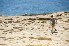 年轻男孩走在多岩石的海滩,在蓝色海旁边,镶边衬衣的 免版税库存照片