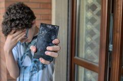 年轻男孩,哀伤和绝望为他的智能手机 免版税库存照片