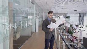 年轻男性专家在运作的过程中看文件,站立在现代汽车中心,读协议,在 股票录像
