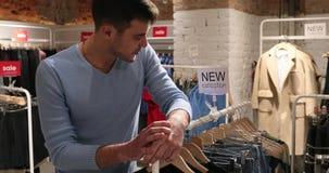 年轻男性卖主在衣裳商店摆在 股票录像
