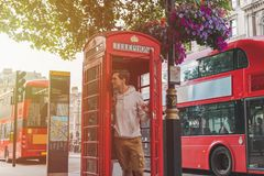 年轻男性在看从有红色公共汽车的一个电话亭的伦敦在后面 免版税库存照片