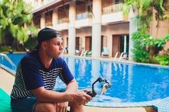 年轻男性录影博客作者创造他的渠道的录影内容 用户的录影射击,当坐由水池时 ? 免版税库存图片