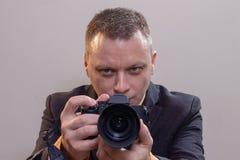年轻男性录影摄影师,摄影师,拍摄录影或拍在照相机的一张照片 库存图片
