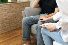 年轻男性患者坐有哀伤的面孔的沙发与心理学家协商 免版税图库摄影