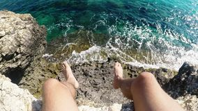 年轻男性探险家第一人透视坐岩石在海上的峭壁边缘 股票视频