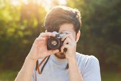 年轻男性摄影师尝试使的照片减速火箭的照相机室外,捉住在宗旨的美好的风景,享受阳光a 免版税图库摄影