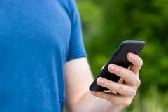 年轻男性收养在他的手上的拿着一个手机 库存图片