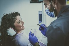 年轻男性牙医准备好手术的患者 免版税库存照片