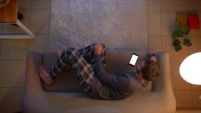 年轻男性看着电视和使用在电话的一个应用程序特写镜头顶面射击作为一遥控说谎在长沙发户内 股票录像