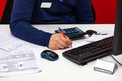 年轻男性管理员谈话在电话在工作,拿着电话与他的耳朵和同时做笔记在本文 免版税库存图片