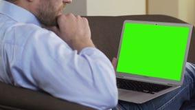 年轻男性键入在有绿色屏幕的膝上型计算机,沟通在约会网站上 影视素材
