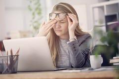 年轻疲乏的职业妇女在工作 库存图片