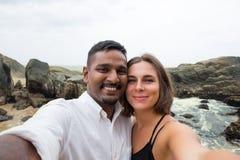 年轻白种人做selfie的妇女和亚裔人在蜂蜜月亮期间在斯里兰卡在海滩 免版税库存图片