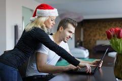 年轻白种人圣诞节的夫妇网上购物由膝上型计算机a 库存图片