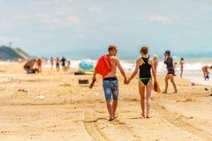 年轻白种人夫妇在晴朗的黑海Blaga海滩胜地饮用的熊沙子走与人的背景的 免版税库存照片