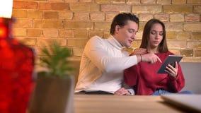 年轻白种人夫妇坐微笑地观看入在家庭环境的片剂的沙发 股票录像